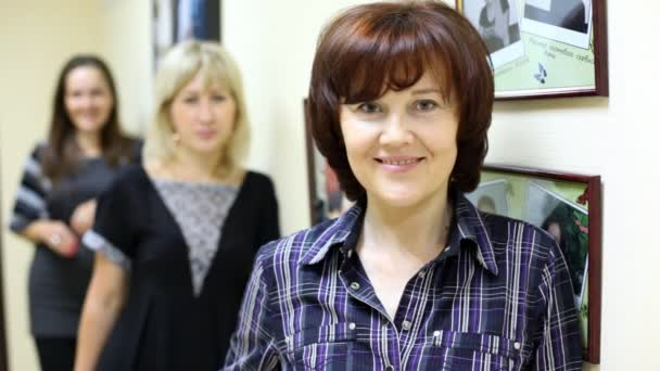 žena pracující v salonu krásy vlídně dívá a usmívá se proti fotografie zaměstnanců