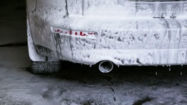 Automobil stojí v mýdlovém roztoku uvnitř garáže mytí aut