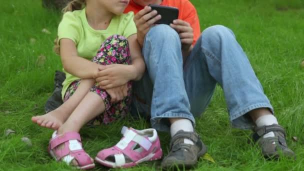 dvě děti chlapec a dívka sedí v trávě vedle parkoviště