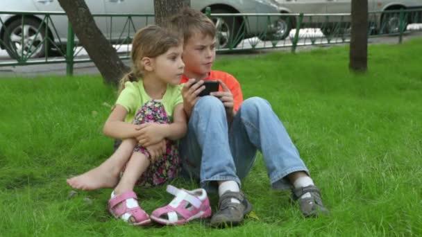 dvě děti sedět spolu, sestra sleduje, jak bratr hraje