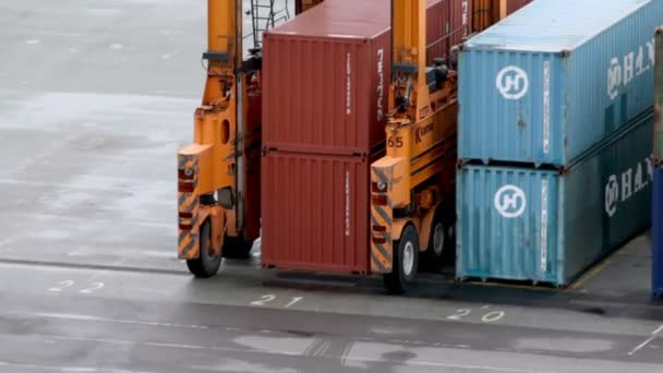 stroj s několika koly jezdí mezi kontejnery v přístavu