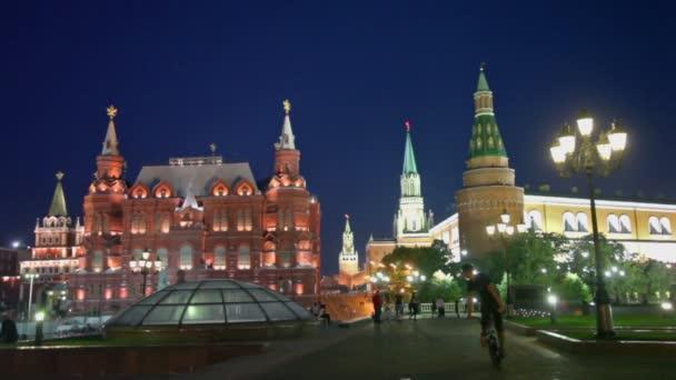 Bicyclist and pedestrians walk by Manezhnaya square near kremlin