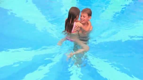 chlapec bere svou malou sestru a hází ji do bazénu vodu