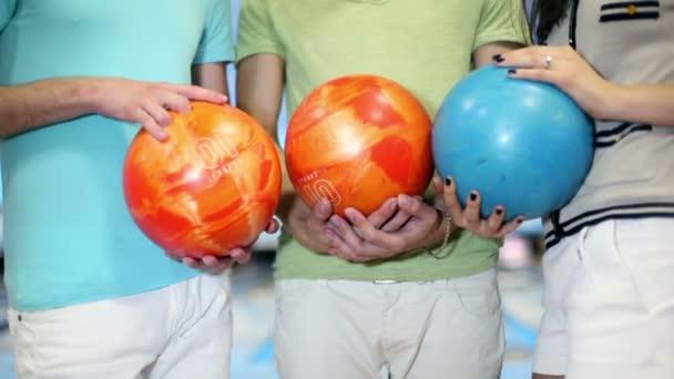 dva chlapci a jedna dívka drží bowlingové koule, detailní zobrazení