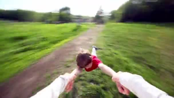 Kézzel tart fű fölött repül a kis fiú