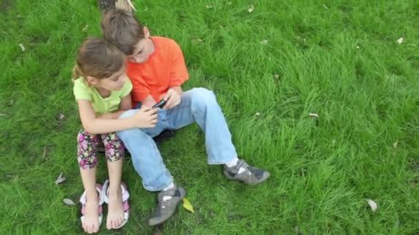Schwester schaut zu, wie Bruder mit digitalem Spiel auf Handy spielt