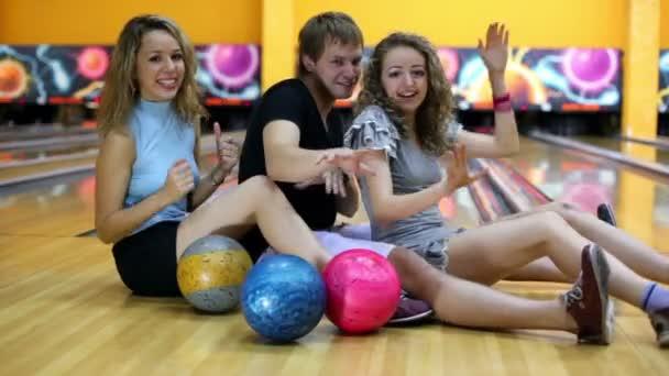 Dvě holky s jedním klukem sedět na podlaze a tanec na bowling klub