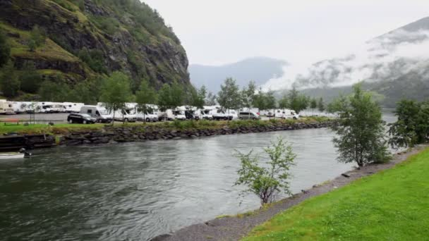 Camping on shore of river which flow into fiord near mountain