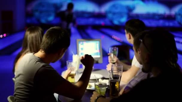 mladý muž dělá udeřit v bowling hry, pobrukovat jeho přátel na zdraví