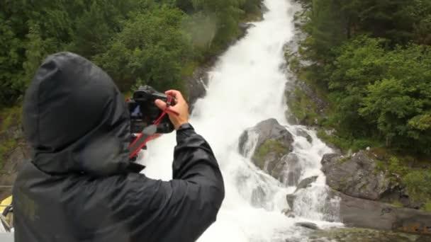 Osoba v pláštěnce fotografie připadá na dřevo rocks