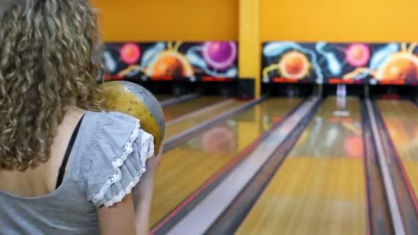 dívka hází bowlingovou kouli porazit kuželky a pak skočí