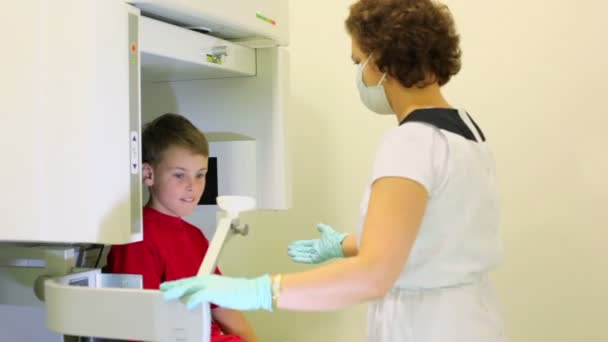 Doctor leads boy in medical diagnostic apparatus and fixes head