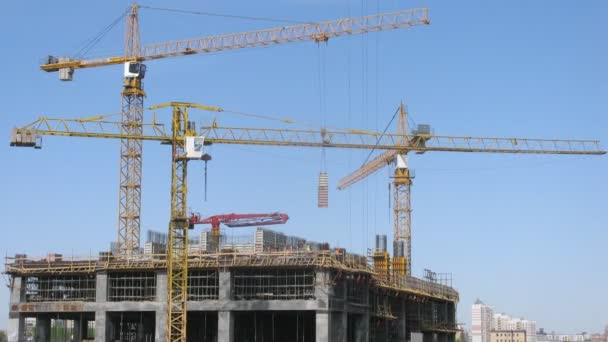 Three cranes stand on construction of skyscrapers, time lapse