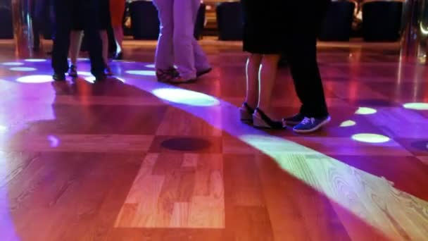 Dancing couples of feet close up in evening in nightclub