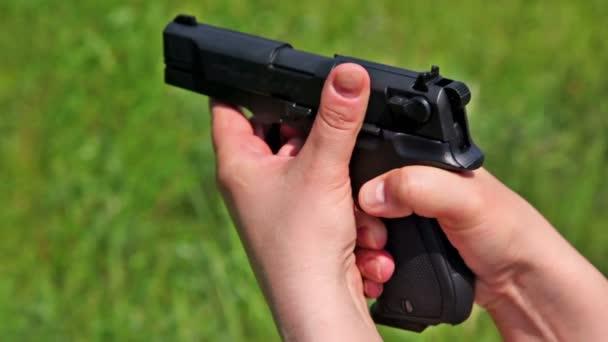 Nő rendelkezik fekete fegyvert, és lő a fű háttér