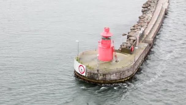malý maják stojící na platformě uprostřed vody