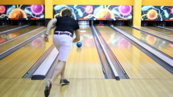 mladý kluk hází bowlingovou kouli a porazí všechny kuželky