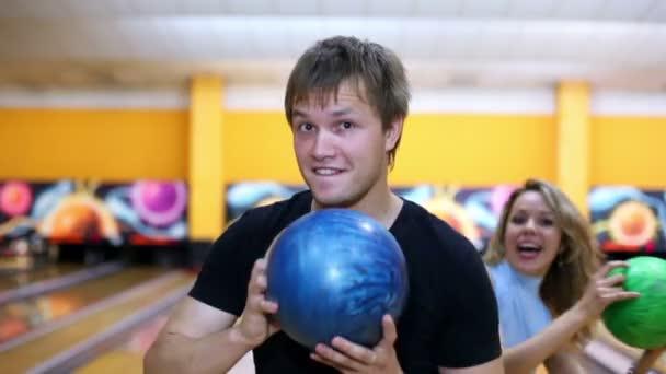 Dvě dívky stojí za chlapce a tanec s bowlingové koule