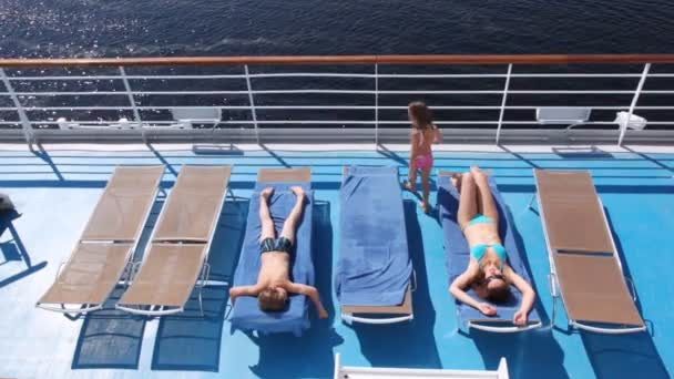 Mother, daughter and son sunbathe on board ship