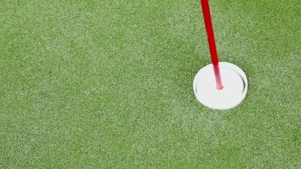 Malý bílý míček projde poblíž vlajky v minigolfu