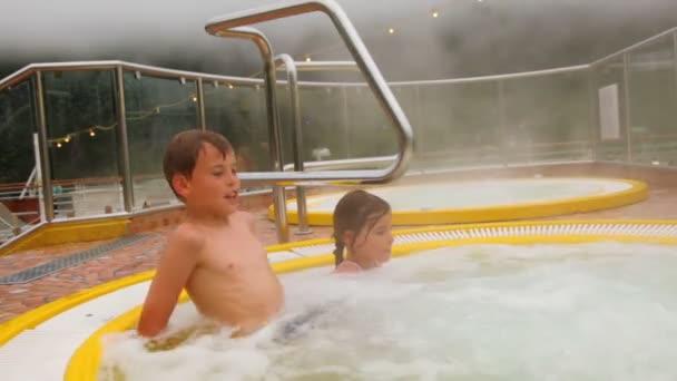 zwei Kinder sitzen im Pool mit heißem Wasser, Dampf Abdeckung rund um