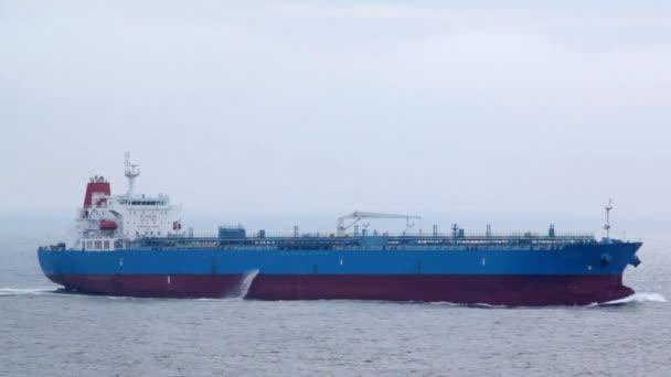 Dlouhé červené a modré tanker plující na vlnách v oblačném počasí
