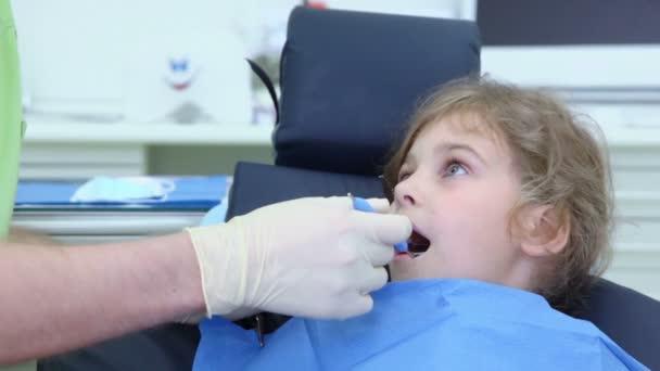 Dentist checks teeth of girl by dental mirror in surgery