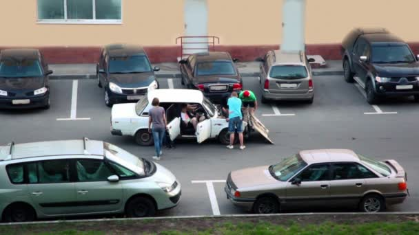 Several boys stand near old car with open hood and try to fix it