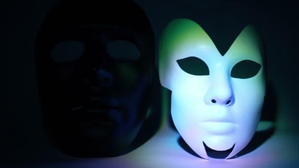 Dvě divadelní masky černé a bílé ozářenou světlem
