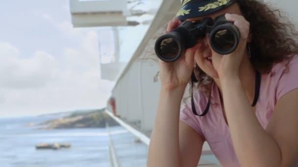 Žena stojí na palubě s dalekohledem během plavby