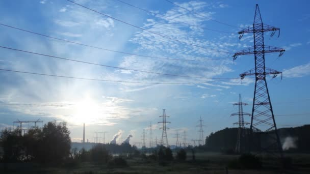 Power transmission lines poles stand against pipes of plant, day