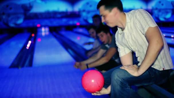 muž drží bowlingovou kouli a pak vyvolá, přátel ho podporují