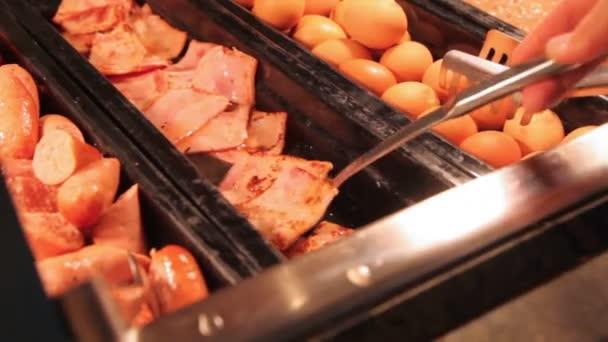 Misky s kusy klobásy a vejce a lžíci brát kus