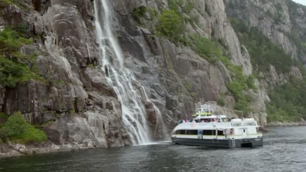Turisté na palubě lodi, které stojí v blízkosti rock s vodopádem