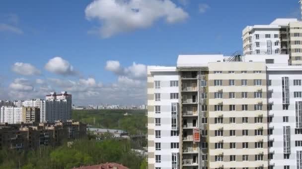 nové stavby stojí proti modré obloze a plovoucí mraky