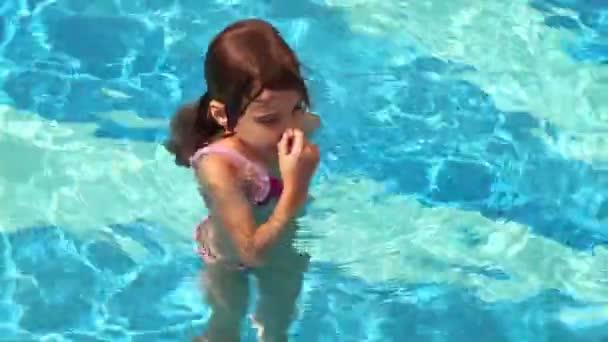 Malá holčička vrhá do vody v bazénu a plavání s mnoha stříkance