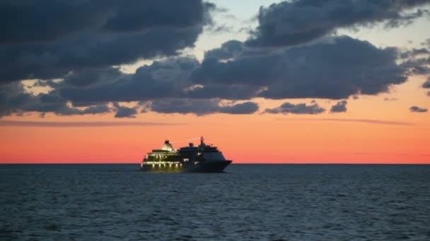 Nave da crociera con illuminazione galleggia nel mare al tramonto
