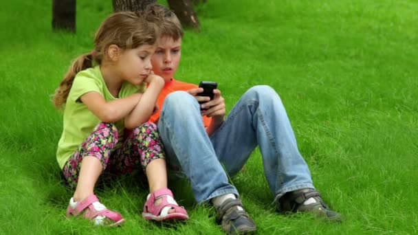 Two kids sit together, boy plays with digital game on cell phone