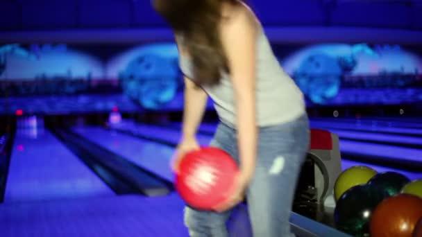 mladá dívka hází bowlingovou kouli porazit kuželky v tmavém klubu