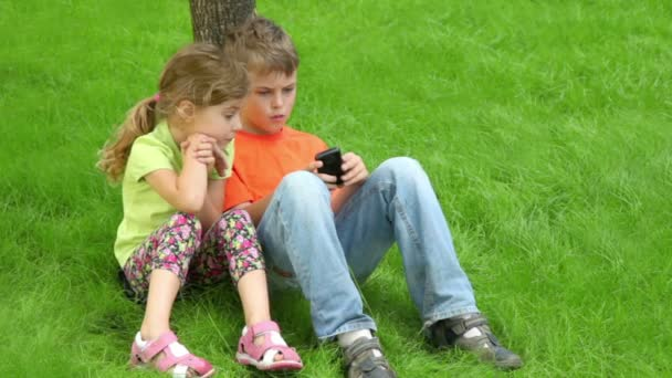 Két gyerek együtt ülni fű fa közelében