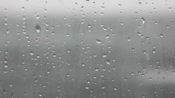 Wassertropfen auf der Glasoberfläche mit Wasser-Strömung außerhalb