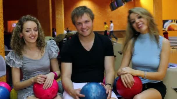 Chlapec s dvěma dívky sit a houpe s míčky v bowling Clubu