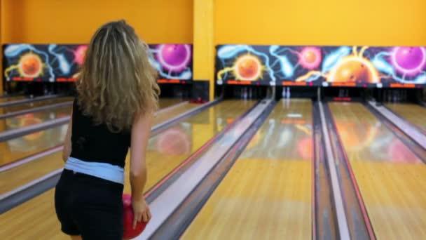 dívka hází bowlingovou kouli porazit dvojice kuželky, ale chyběl