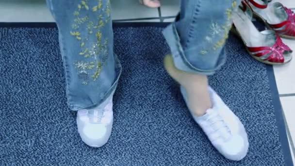 Piedi della donna in scarpe nuove e vecchio paio non sostare sul tappeto