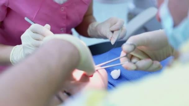 Doktor nastaví jehlu v svorku pro sew rány v ústech Girl