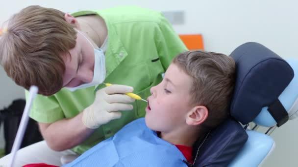 Zubař při kontrole zubů chlapce zubní zrcátko v chirurgii