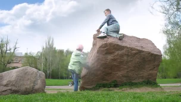 Kinder sitzen auf großem Stein im Botanischen Garten