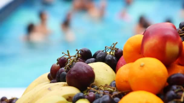 Oranges, apples, bananas, grapes close up in front of pool