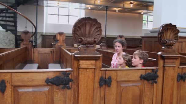 Matka s dětmi kluk a holčička sedět na lavici v katedrále