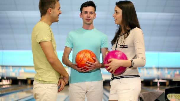 tři studenti hrát bowling, chlapec hodí míč a Mine kuželky